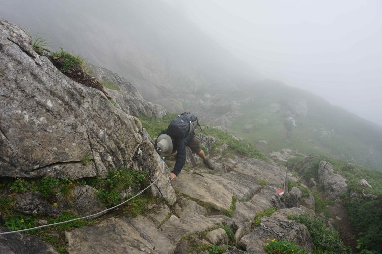 Man in hiking gear climbing down a cliff in the mist using a wire rail.