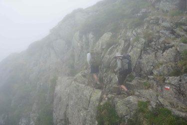 Two hiking men walking along a steep cliff using a mountain hand rail