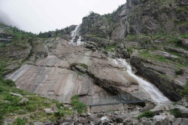 Huge waterfall coming down a massive slab of rock with a bridge crossing it at the bottom