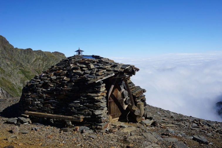 Round stone hut on a mountain above the cloud