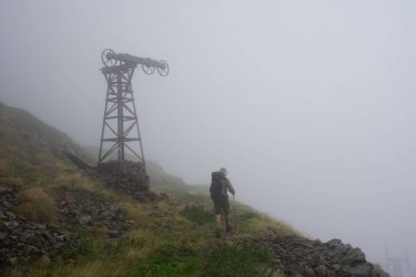 Man in hiking clothes walking past an old mining tower in the mist.
