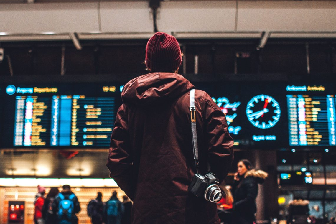 a person stands in the airport looking at the flight board