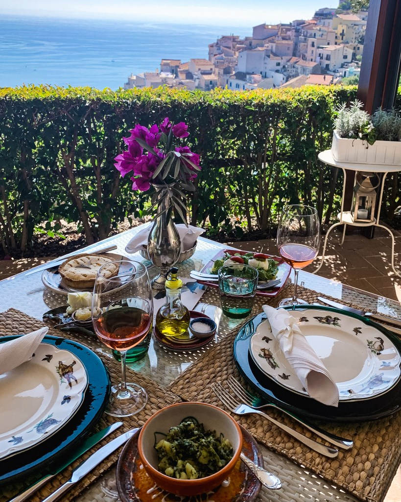 the view of the Amalfi Coast from a terrace with a table set for a multi-course lunch with wine