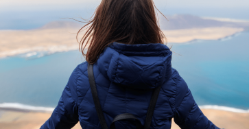 An image of a woman standing alone looking off into the distance.