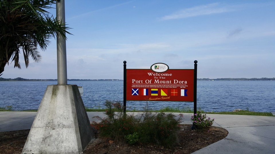 Shows the sign for Port Dora and a view of the lake