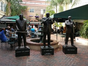 Shows a statue of three musicians on Bourbon Street in New Orleans