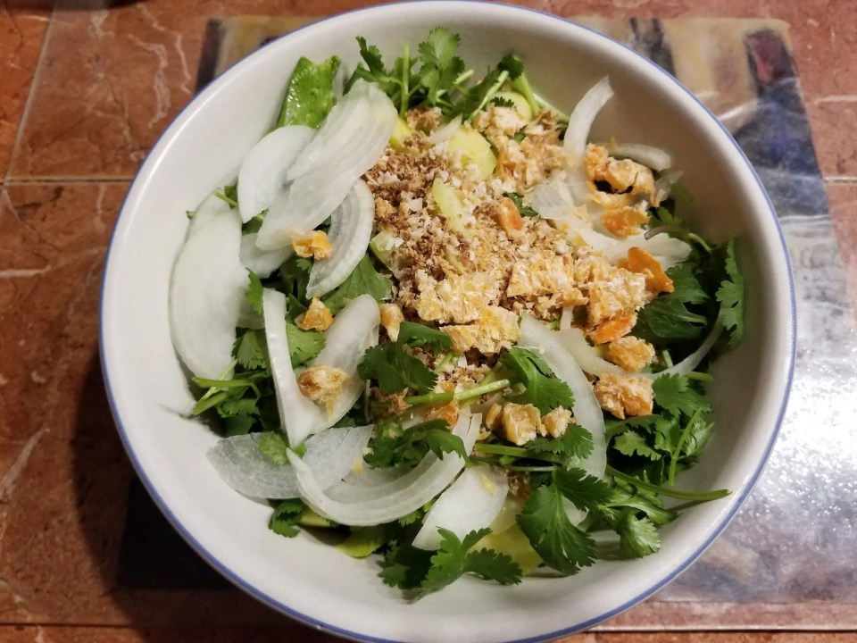 Shows a picture of Thai cooking, a green mango salad