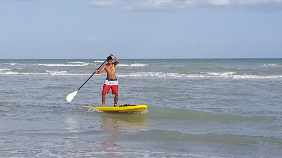 a young man paddle boarding at the beach in Sanibel Florida