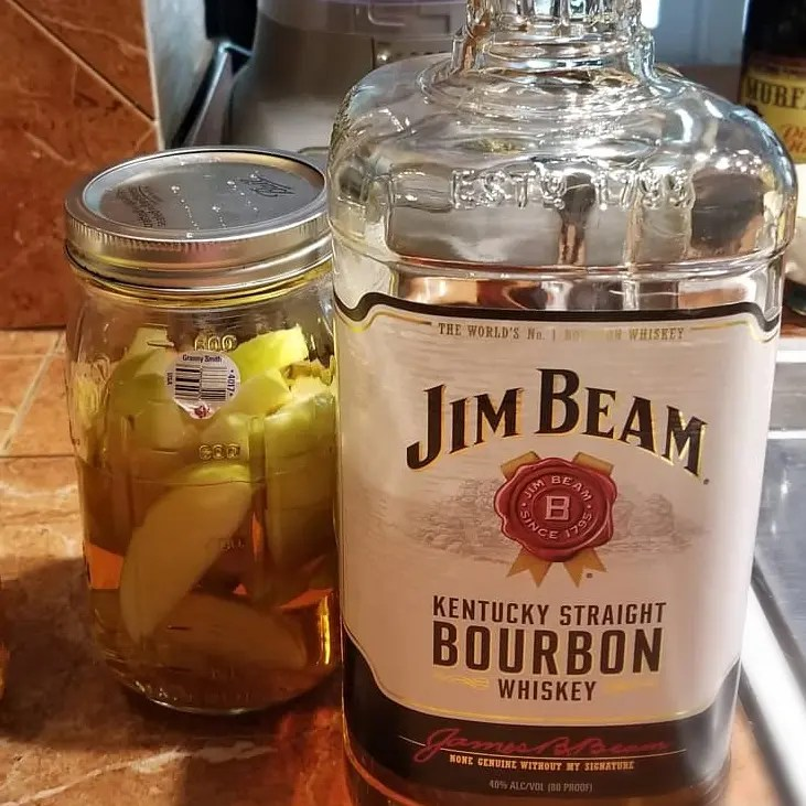 How to infuse bourbon with apples, shows a bottle of Jim Beam with a mason jar filled with sliced apples and bourbon