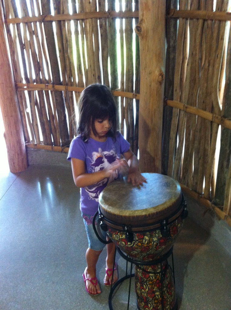 Looking for things to do in south Florida for families? Here is a girl learning about African cultures by playing a drum at Young at Art