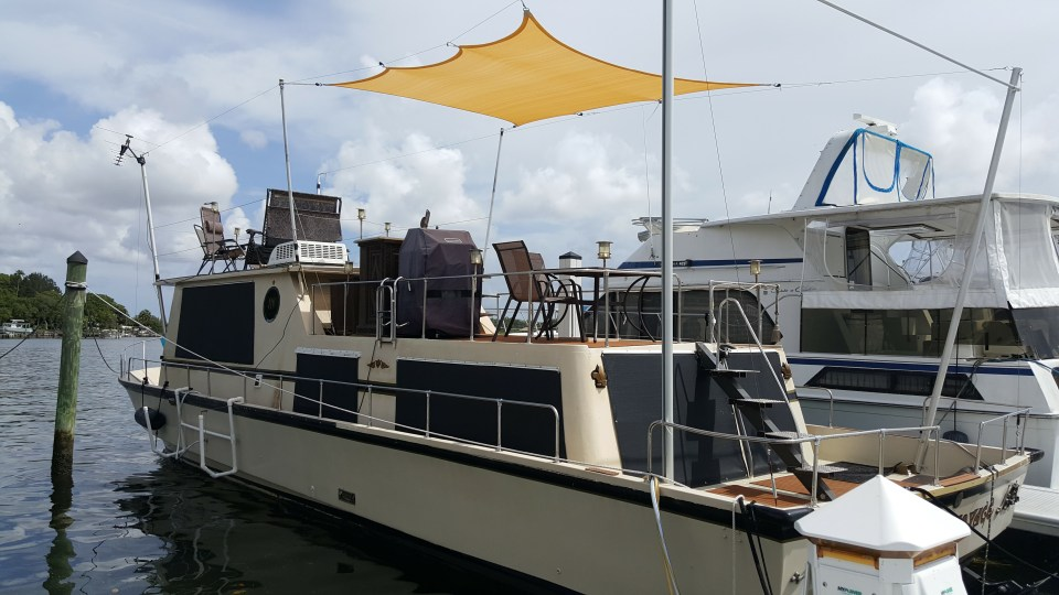 a houseboat at dock with several decks ready for romantic getaways in Florida