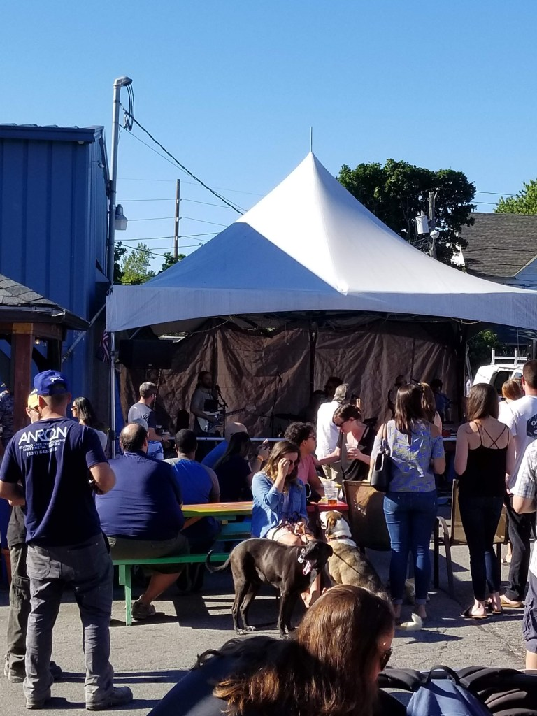 people enjoying live music while drinking beer outside Bluepoint Brewing Company