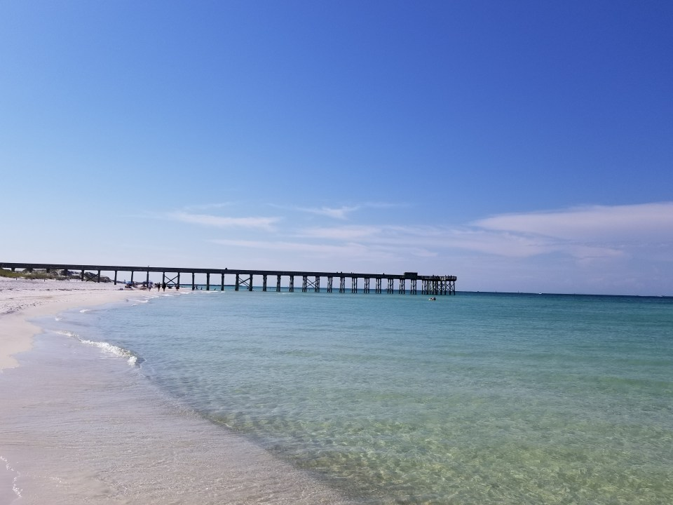 shows a picture of sand and the pier over the water in Panama City Beach