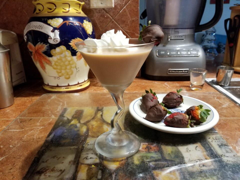 shows a sexy drink in a martini glass filled with a chocolate beverage, topped with whipped cream and a chocolate covered strawberry