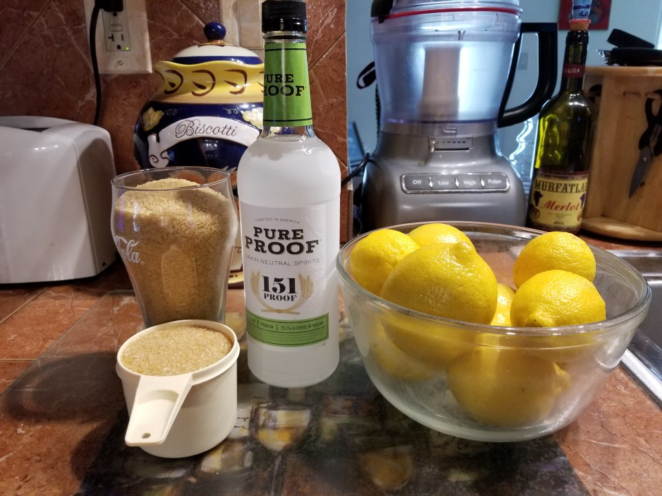 shows sugar, a bottle of 151 proof alcohol and a bowl of lemons, ingredients needed to make limoncello