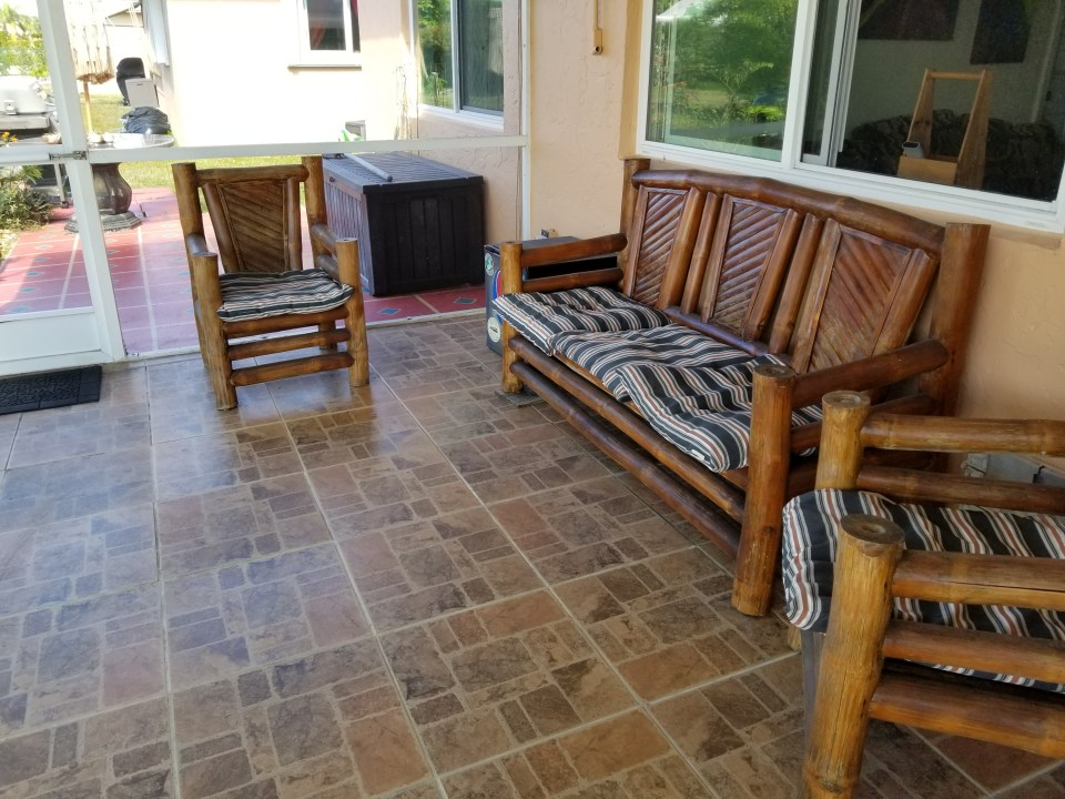 outdoor screened room with tiki loveseat and chairs for living in south Florida during mosquito season