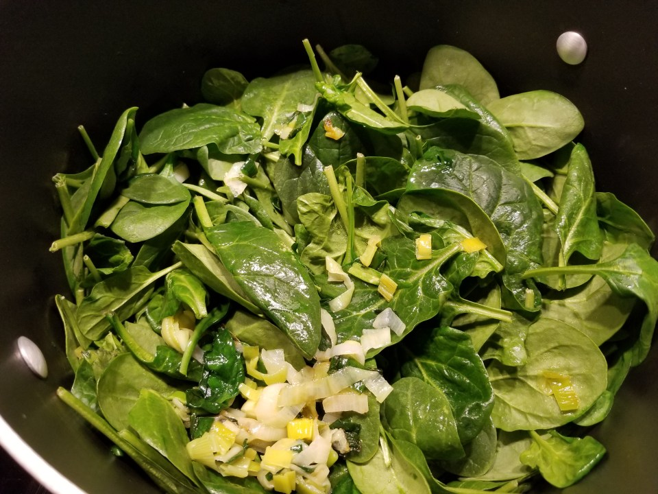 spinach and onions cooking in a frying pan