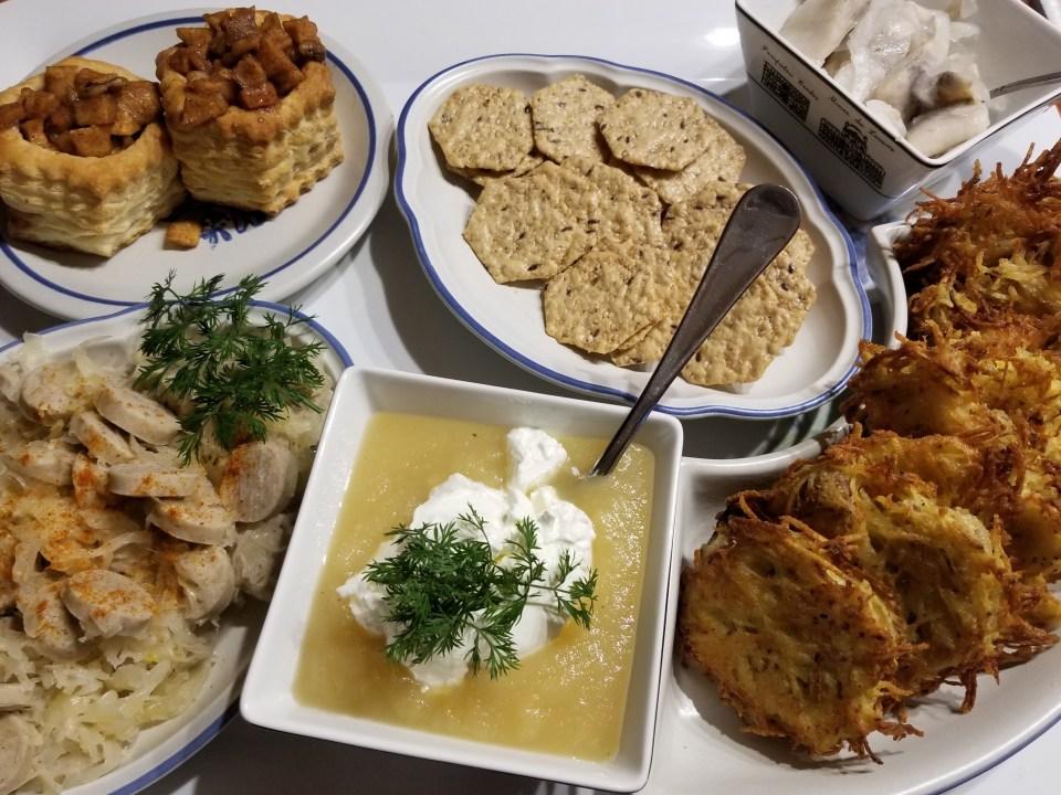 Charcuterie platter from Austria displaying herring, potato pancakes, bratwurst with sauerkraut and apple strudel