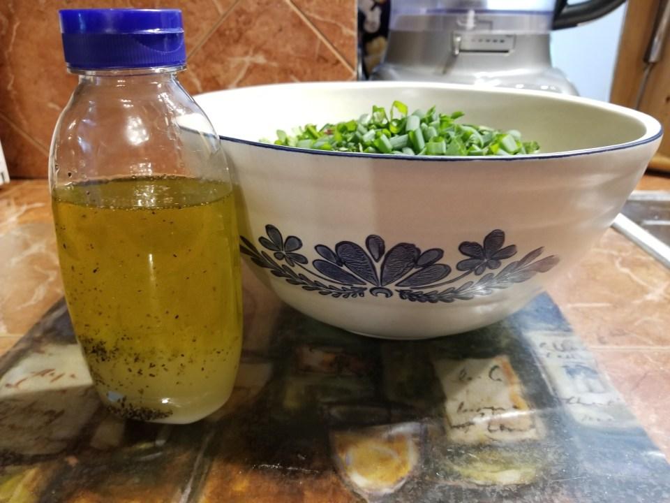 bottled homemade lemon dressing with lettuce salad as part of Easter dinner traditions in Greece