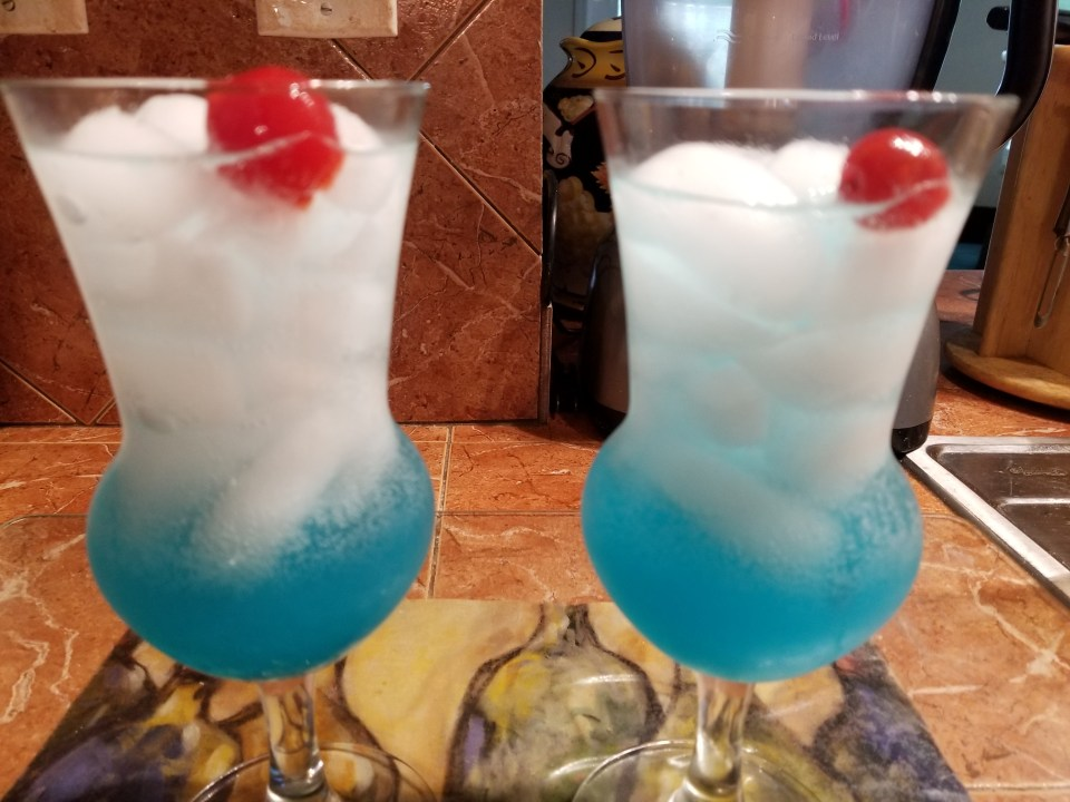 shows two red white and blue drinks, blue on the bottom, white ice, and cherry on top