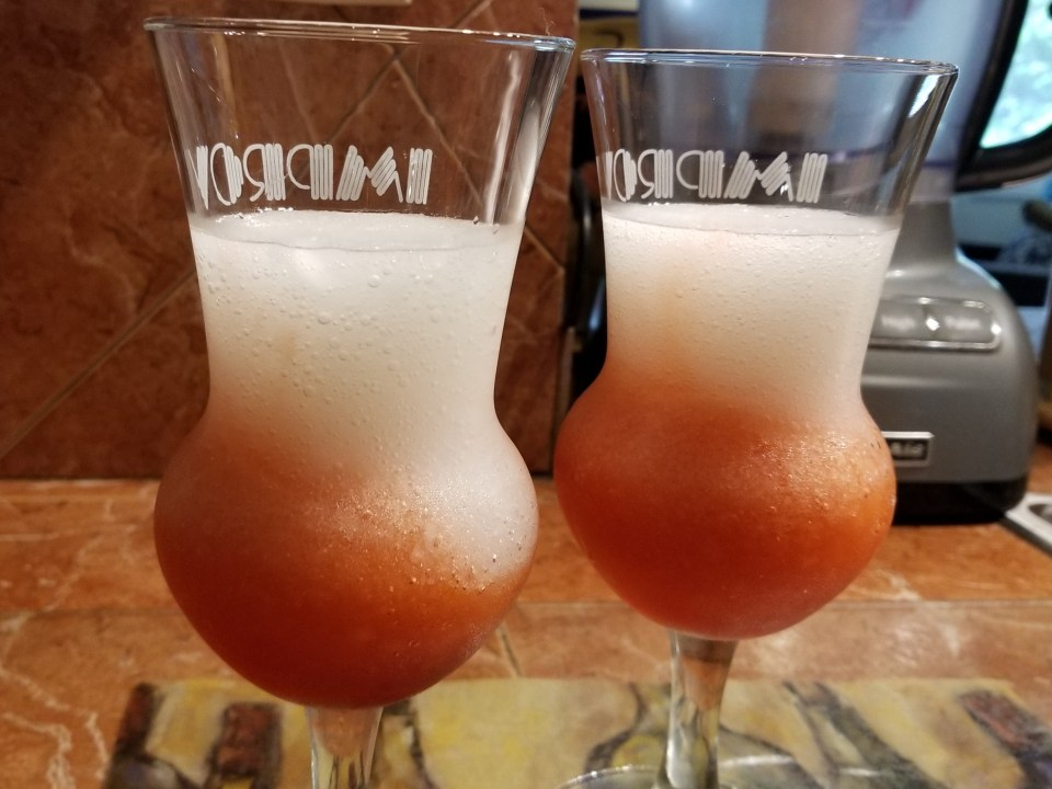 2 glasses filled with red slush on the bottom and then white frozen drink on top 2/3 fill in preparation for red white and blue drinks