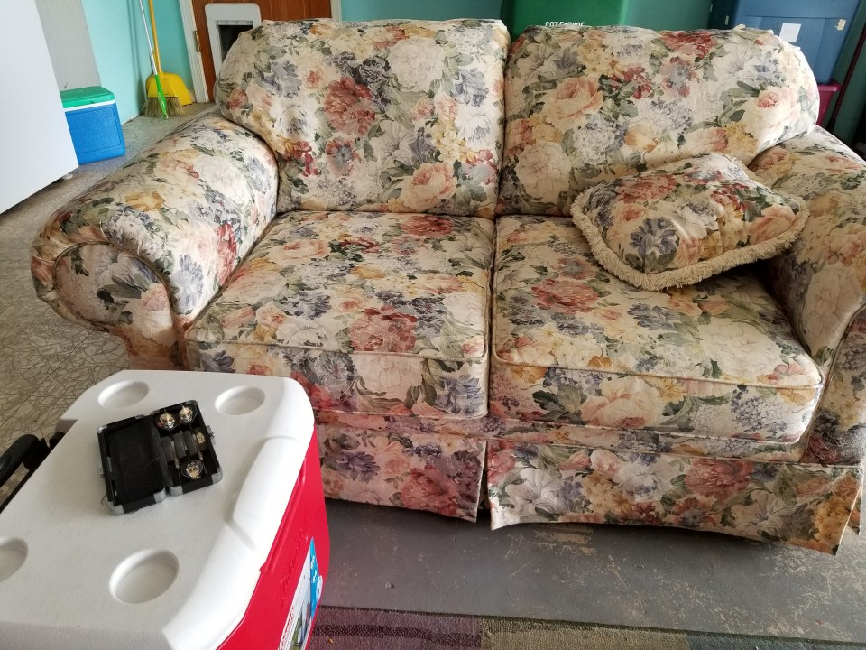 second hand couch and cooler end table for making a garage into a mancave