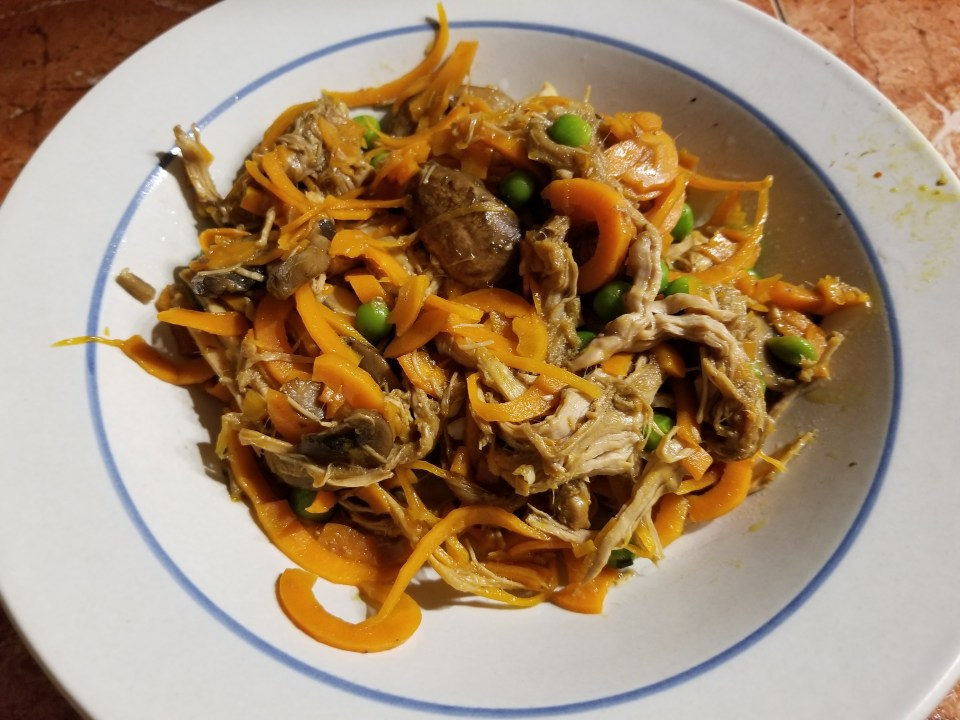 carrot lo mein chicken in a bowl with peas and mushrooms.