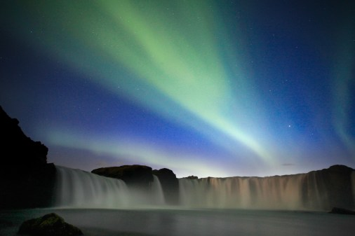 Aura borealis over Iceland waterfall