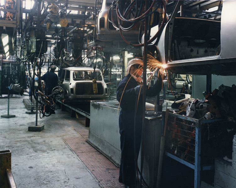 Colour image of a man wearing protective headgear welding a section of the body of a car. Sparks are flying from the vehicle body and another vehicle shell can be seen in the background.