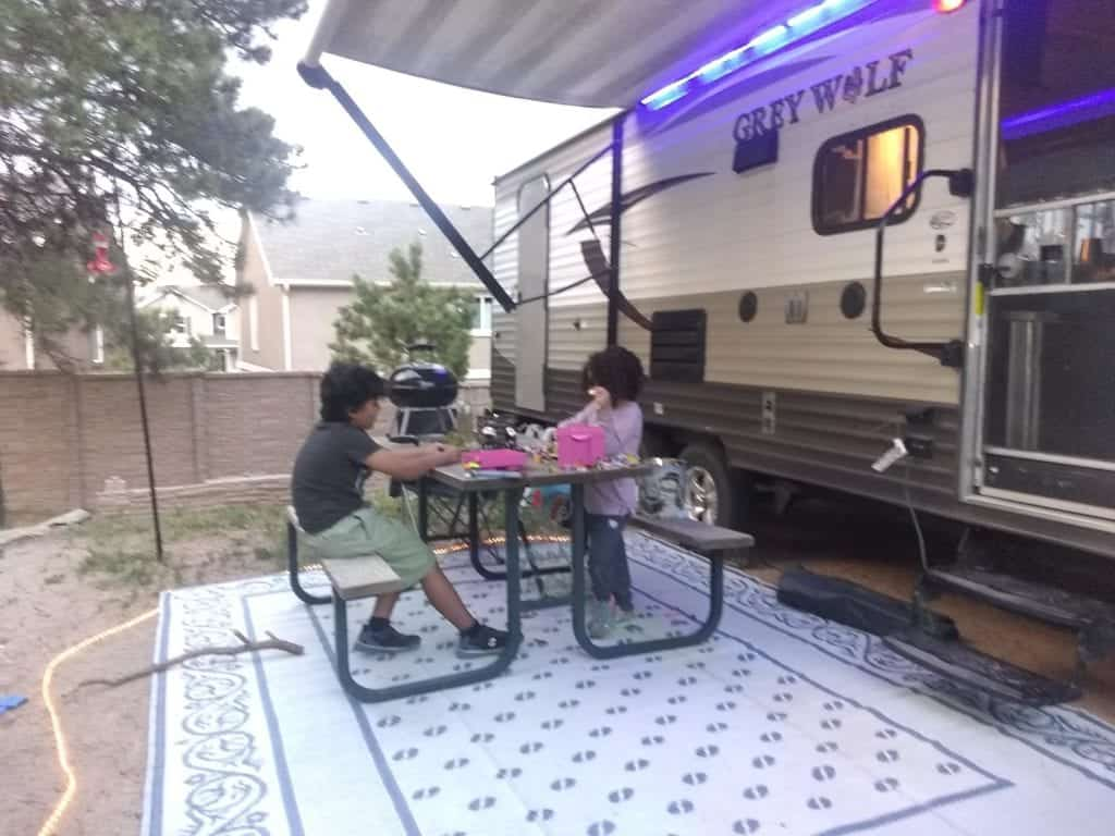 Two children sit at a picnic table playing Legos under the awning of their travel trailer.