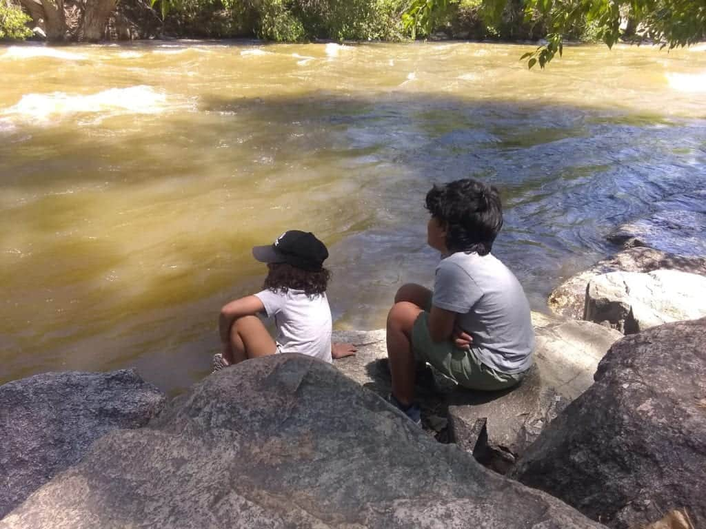 Two children sit on rocks gazing upon the Arkansas River in Salida, Colorado.
