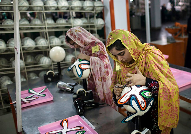 6_an employee adjusts outer panels on a soccer ball