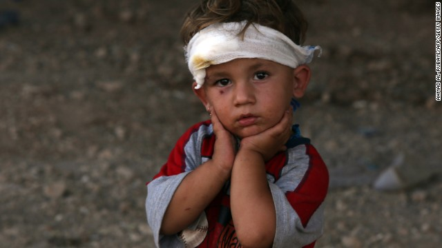 An Iraqi Yazidi child, whose family fled their home a week ago when ISIS militants attacked the town of Sinjar, looks on at a makeshift shelter on August 10 in the Kurdish city of Dohuk in Iraq's autonomous Kurdistan region.