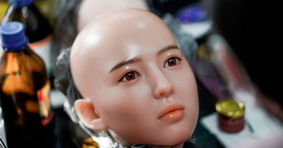 """This photo taken on February 1, 2018 shows a worker painting the face of a silicone doll at a factory of EXDOLL, a firm based in the northeastern Chinese port city of Dalian. With China facing a massive gender gap and a greying population, a company wants to hook up lonely men and retirees with a new kind of companion: """"Smart"""" sex dolls that can talk, play music and turn on dishwashers."""