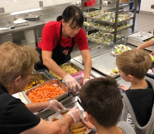 Food service staff serve food to students in lunch line.