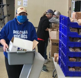 School food service workers prepare grab-and-go bags of food.