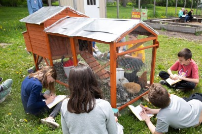 Small chicken coop with students sitting nearby drawing.