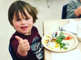 Preschool boy gives thumbs up for locally sourced lunch meal.