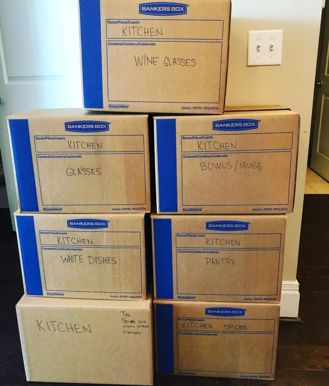 Moving boxes stacked against wall with labels by room. Photo by Instagram user @chaos.organizer
