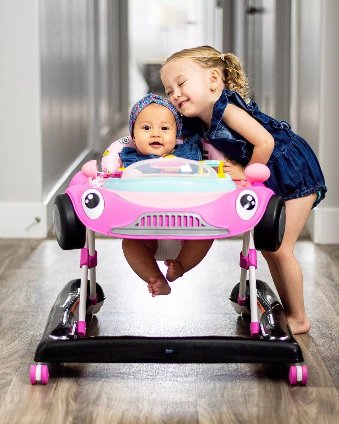Baby in baby walker next to big sister. Photo by Instagram user @vivimccoy_
