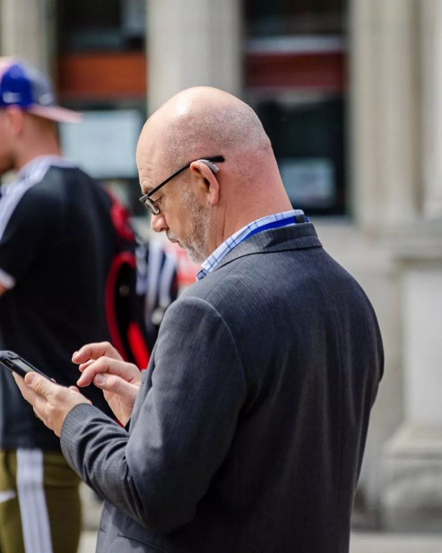 Middle-aged man in suit texting on phone. Photo by Instagram user @frankson_photography