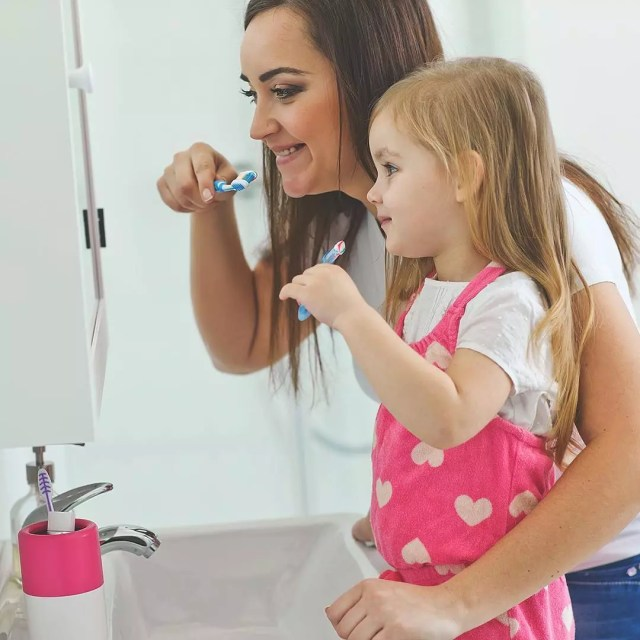 Mom and daughter brushing teeth in front of mirror. Photo by Instagram user @rembrandtwhitens
