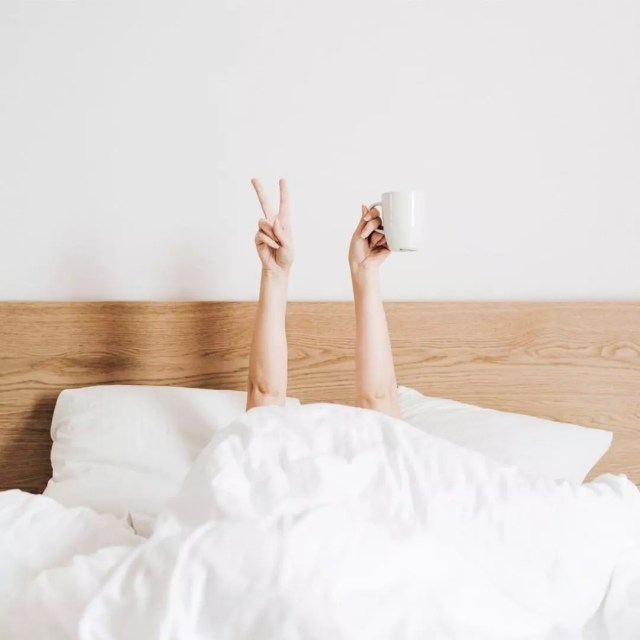 Woman lying in bed with coffee cup and peace sign fingers. Photo by Instagram user @rhondahamel.ca