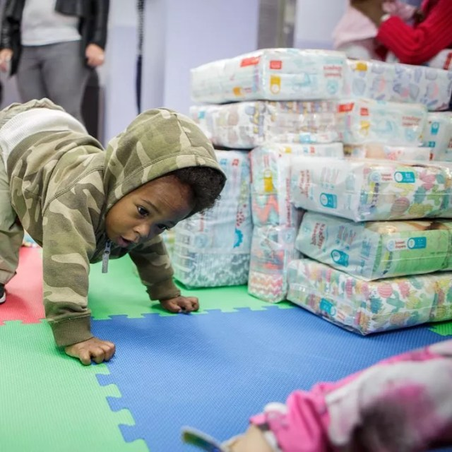 Young Child Crawling in Front of Stack of Donated Packs of Diapers. Photo by Instagram user @nycmammasgiveback