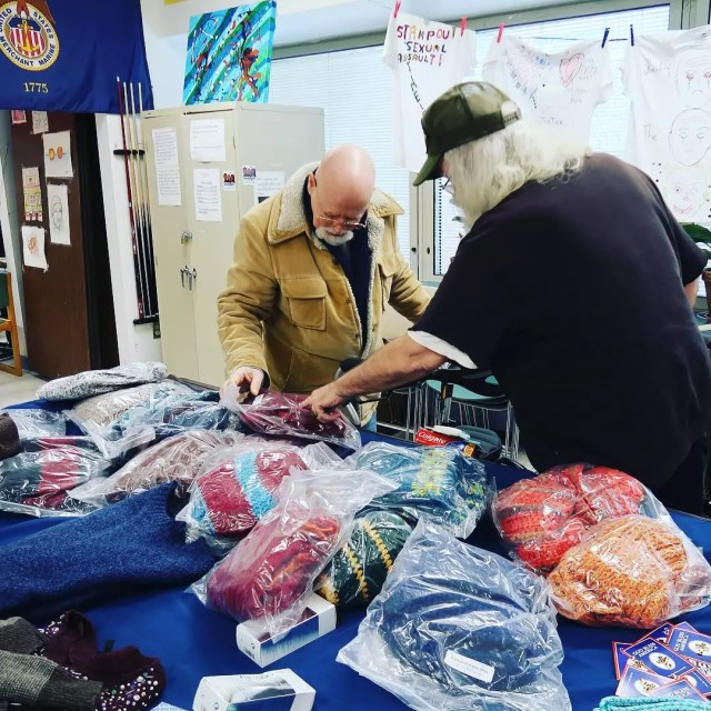 Men Looking Through Bags on Donated Clothes on Tables. Photo by Instagram user @uwvc
