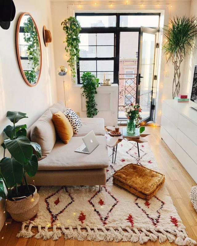 Small apartment living room with plants hanging from ceiling and white patterned rug. Photo by Instagram user @viktoria.dahlberg