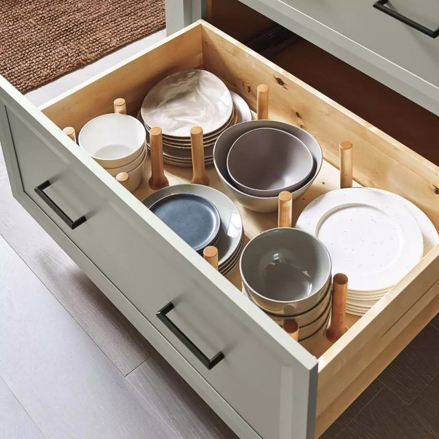 Kitchen drawer with peg organizer for dishes. Photo by Instagram user @masterbrandcabinets
