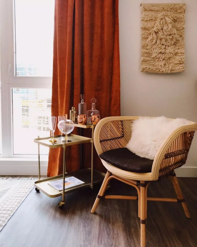 Bar cart next to living room chair. Photo by Instagram user @laplazavillage