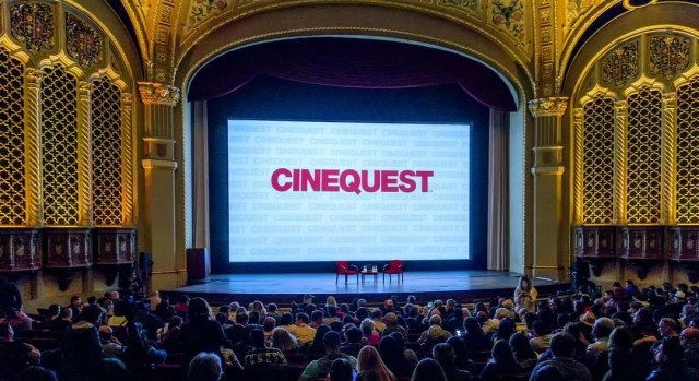 View of empty stage with two red chairs and a large screen with CINEQUEST shown on it and a full crowd in the audience. Photo by Instagram user @cinequestorg