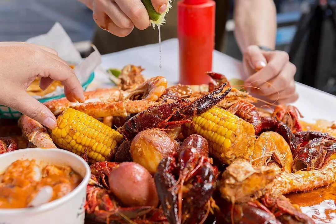 Closeup of crab boil with corn, potatoes and more with two people reaching for it. Photo by Instagram user @boilingcrab